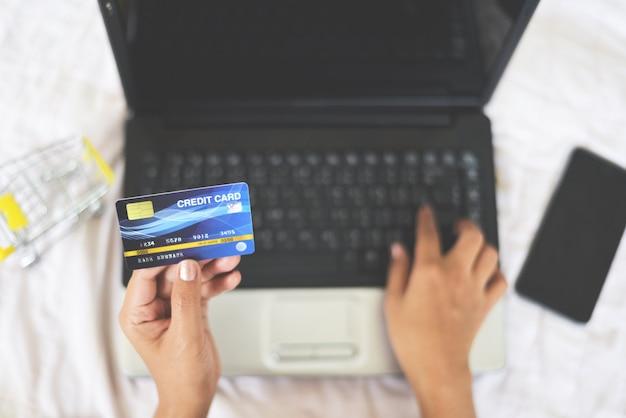 Mãos de mulher segurando um cartão de crédito e usando o laptop para compras on-line com carrinho de compras