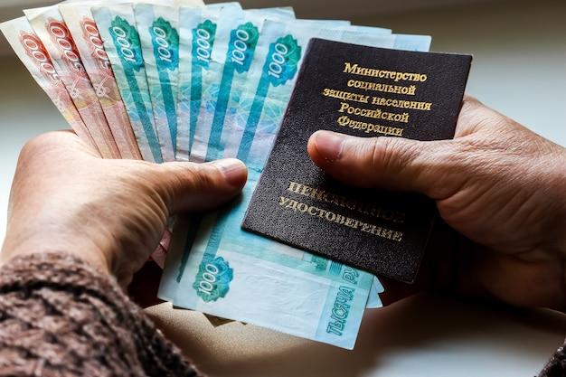 Mãos de mulher segurando um certificado de pensão russo e rublos russos.