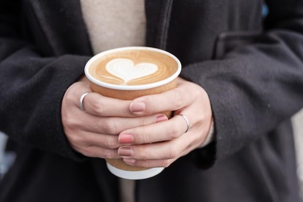Mãos de mulher segurando um copo de papel de café quente, arte de café com leite de forma de coração. amor, feriado, dia dos namorados e conceito de recipiente plástico grátis