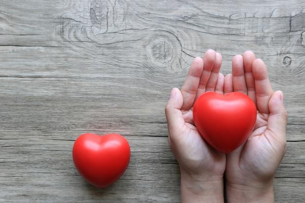 Mãos de mulher segurando um coração vermelho na mesa de madeira