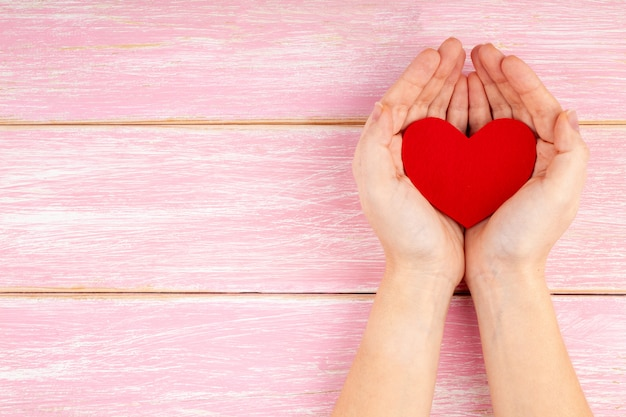 Mãos de mulher segurando um coração vermelho no fundo rosa de madeira - cuidados de saúde, amor