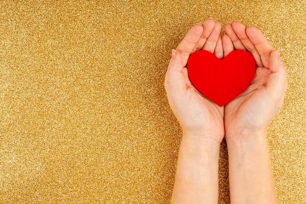 Mãos de mulher segurando um coração vermelho sobre fundo dourado - cuidados de saúde, amor
