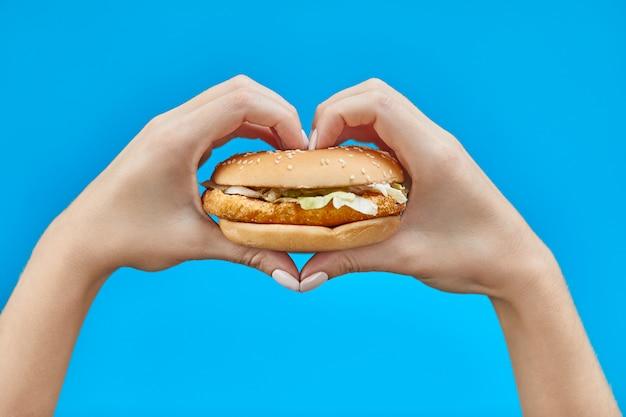 Mãos de mulher segurando um hambúrguer em um azul