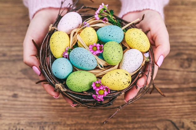 Mãos de mulher segurando um ovo de páscoa pintado em um pequeno ninho