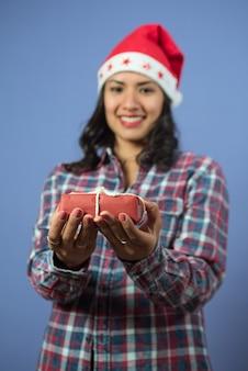 Mãos de mulher segurando um presente de natal