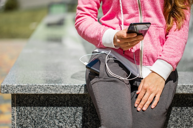 Mãos de mulher segurando um smartphone preto, carregando a bateria do banco de potência externa