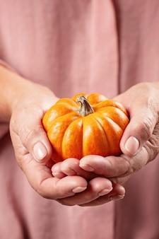 Mãos de mulher segurando uma abóbora