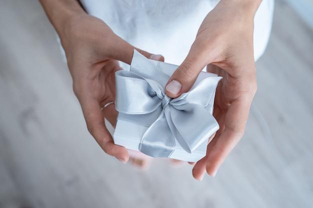 Mãos de mulher segurando uma caixa de presente com laço branco, close-up