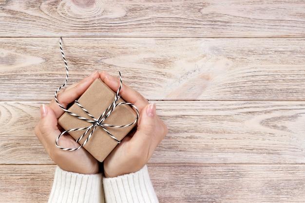 Mãos de mulher segurando uma caixa de presente de natal. presentes de natal e ano novo. feito à mão