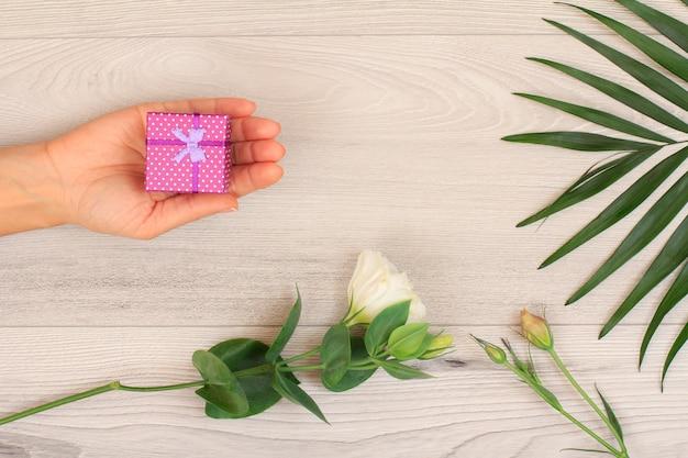 Mãos de mulher segurando uma caixa de presente em fundo cinza de madeira com linda flor e folhas verdes. conceito de dar um presente no feriado ou aniversário. vista do topo.