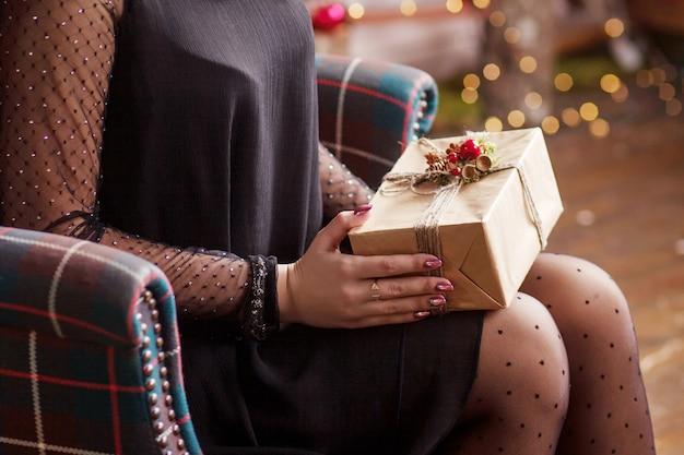 Mãos de mulher segurando uma caixa de presente ouro. cena festiva com bokeh.
