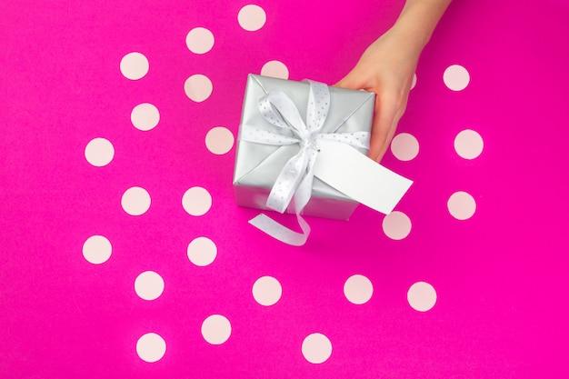 Mãos de mulher segurando uma caixa de presente rosa