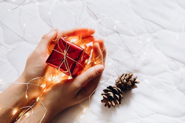 Mãos de mulher segurando uma caixa de presente vermelha com guirlanda clara