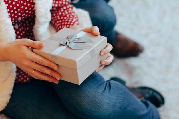 Mãos de mulher segurando uma caixa de presente