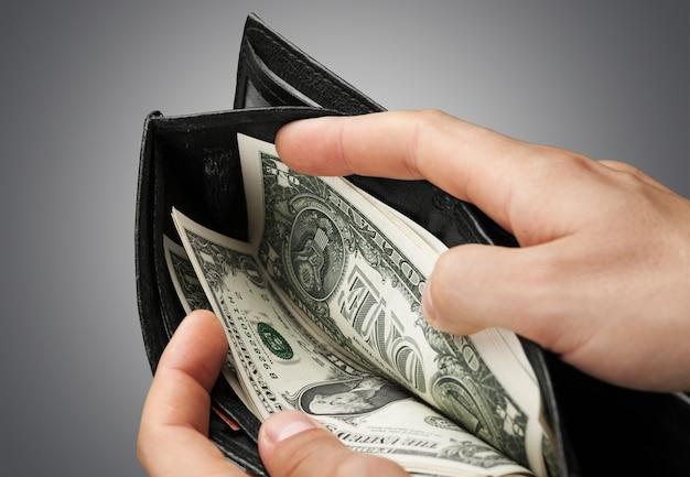 Mãos de mulher segurando uma carteira com dólares. conceito de negócios