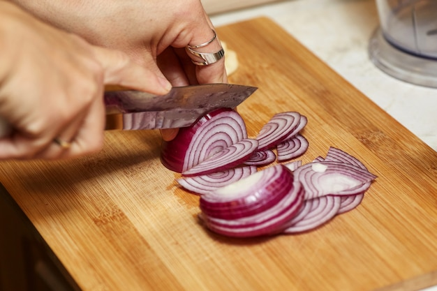 Mãos de mulher segurando uma faca e picar cebola vermelha na cozinha