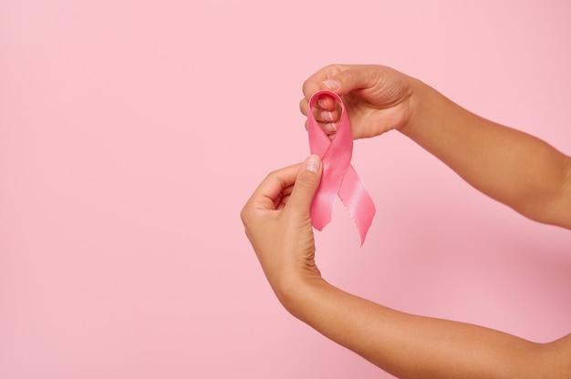 Mãos de mulher segurando uma fita rosa, símbolo do dia mundial da conscientização do câncer de mama, em 1º de outubro. saúde da mulher e o conceito médico, dia rosa de outubro, dia mundial do câncer, dia nacional do sobrevivente do câncer.