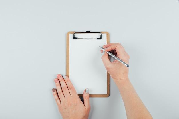 Mãos de mulher segurando uma folha de papel ou caderno e caneta. mesa cinza. configuração plana. conceito de maquete