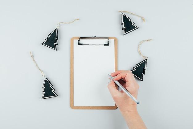 Mãos de mulher segurando uma folha de papel ou caderno e caneta. mesa cinza. vista do topo. conceito de maquete