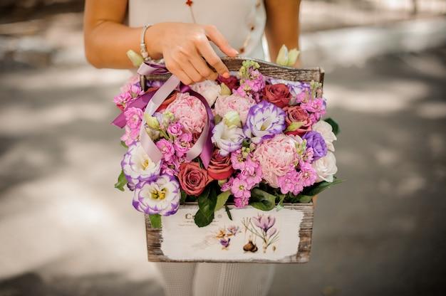 Mãos de mulher segurando uma linda composição de flores