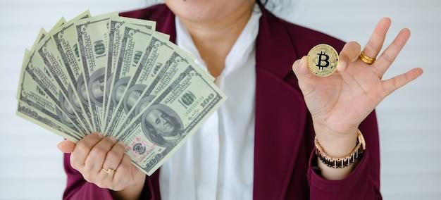 Mãos de mulher segurando uma moeda criptográfica e espalhando o dinheiro das notas de dólar e o gesto de comparação. conceito de investimento em ativos digitais e tesouro da velha escola.