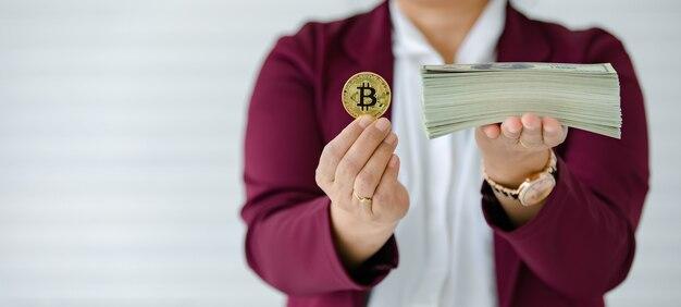Mãos de mulher segurando uma moeda criptográfica e uma pilha de dinheiro das notas e o gesto de comparação. conceito de investimento em ativos digitais e tesouro da velha escola.