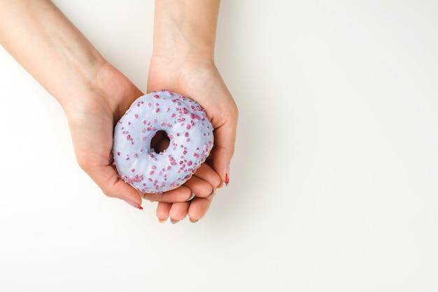 Mãos de mulher segurando uma rosquinha saborosa, vista superior. estilo minimalista, plano.