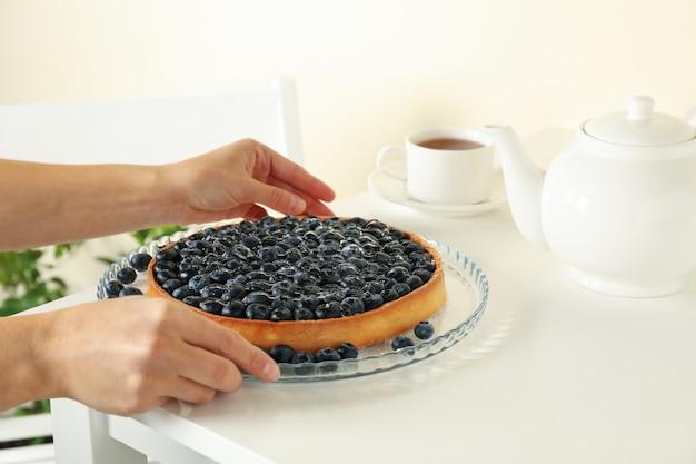 Mãos de mulher segurando uma saborosa torta de mirtilo na mesa branca