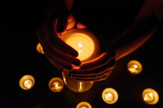 Mãos de mulher segurando uma vela acesa. muitas chamas de velas brilhando. fechar-se.