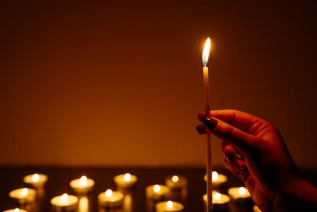 Mãos de mulher segurando uma vela acesa. muitas chamas de velas brilhando.