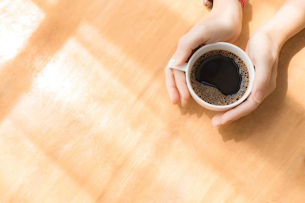 Mãos de mulher segurando uma xícara de café branco