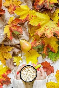 Mãos de mulher segurando uma xícara de chocolate quente com marshmallow em uma mesa de madeira branca com folhas de outono coloridas