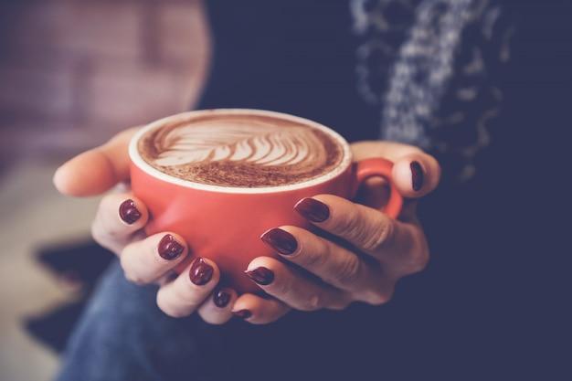 Mãos de mulher segurando uma xícara vermelha de café com leite