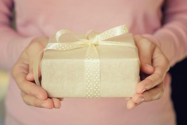 Mãos de mulher segurar uma caixa de presente embrulhado em papel com fita