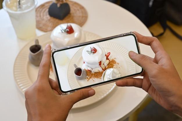 Mãos de mulher tira fotografia de sobremesa com telefone. panqueca e morango com creme.