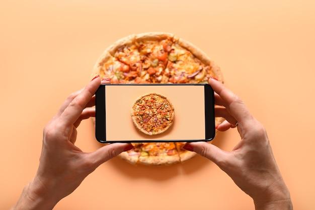 Mãos de mulher tirando fotos de pizza italiana vegana com tomate, mussarela e molho