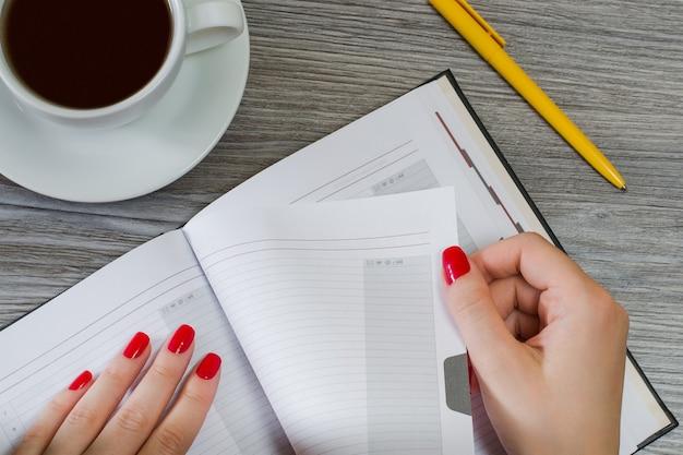 Mãos de mulher tirando uma página de seu bloco de notas. xícara de chá, a caneta está no fundo. foto de visão aérea