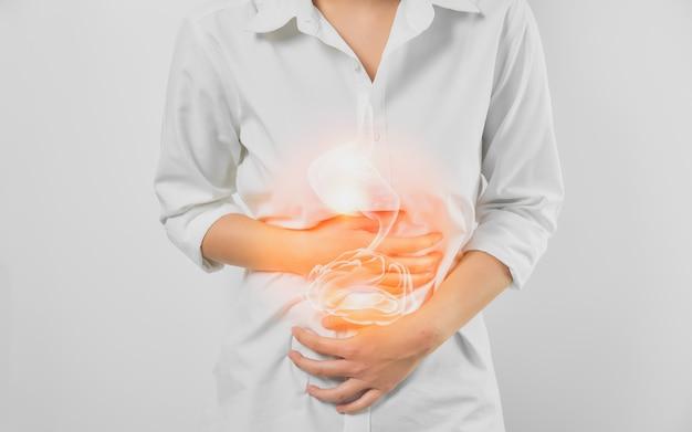 Mãos de mulher tocando a barriga e o estômago doloroso, sofrendo de gastrite crônica em fundo branco