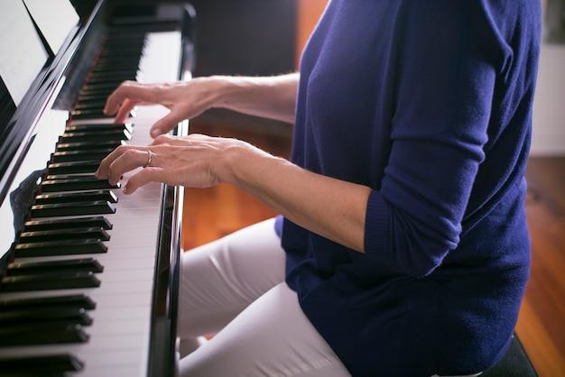Mãos de mulher tocando música clássica no piano.