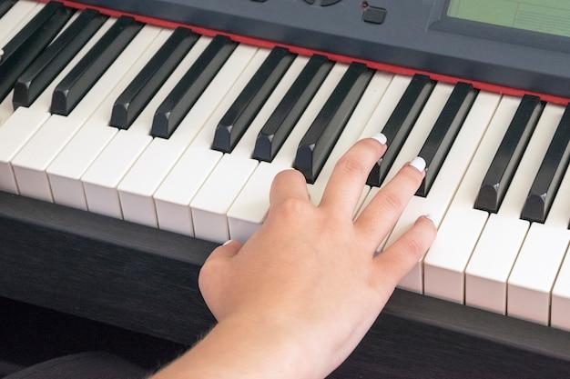 Mãos de mulher tocando piano elétrico