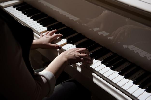 Mãos de mulher tocando um piano, instrumento musical.