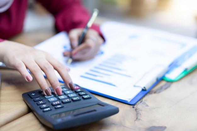 Mãos de mulher trabalhando com calculadora sobre planejamento financeiro pessoal em casa escritório.