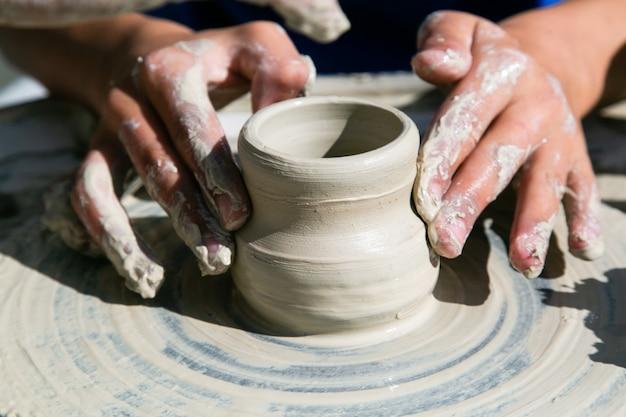 Mãos de mulher trabalhando de cerâmica na roda de oleiro