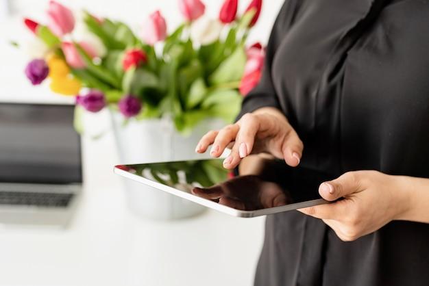 Mãos de mulher trabalhando em tablet digital, balde de tulipas frescas no fundo