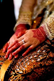 Mãos de mulher tradicional javanesa usando batik e anel de casamento