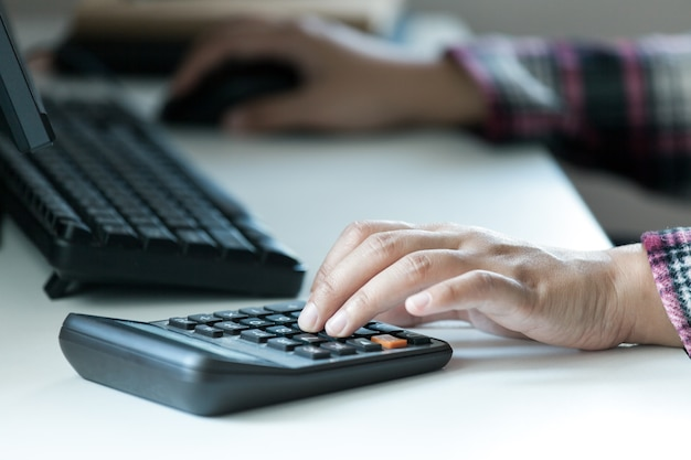 Mãos de mulher usando calculadora na mesa