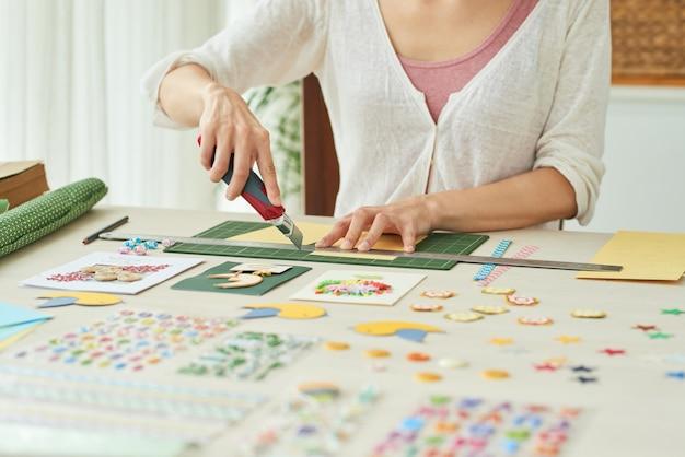 Mãos de mulher usando faca afiada para cortar papel colorido para fazer cartões de aniversário