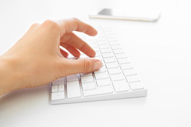 Mãos de mulher usando o teclado no escritório