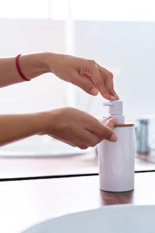 Mãos de mulher usando sabão e lavar as mãos sob a torneira de água