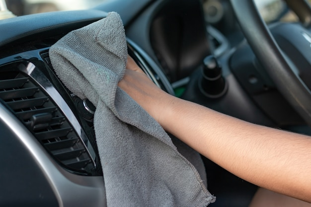 Mãos de mulher usando tecido de microfibra para limpar o interior do carro suv